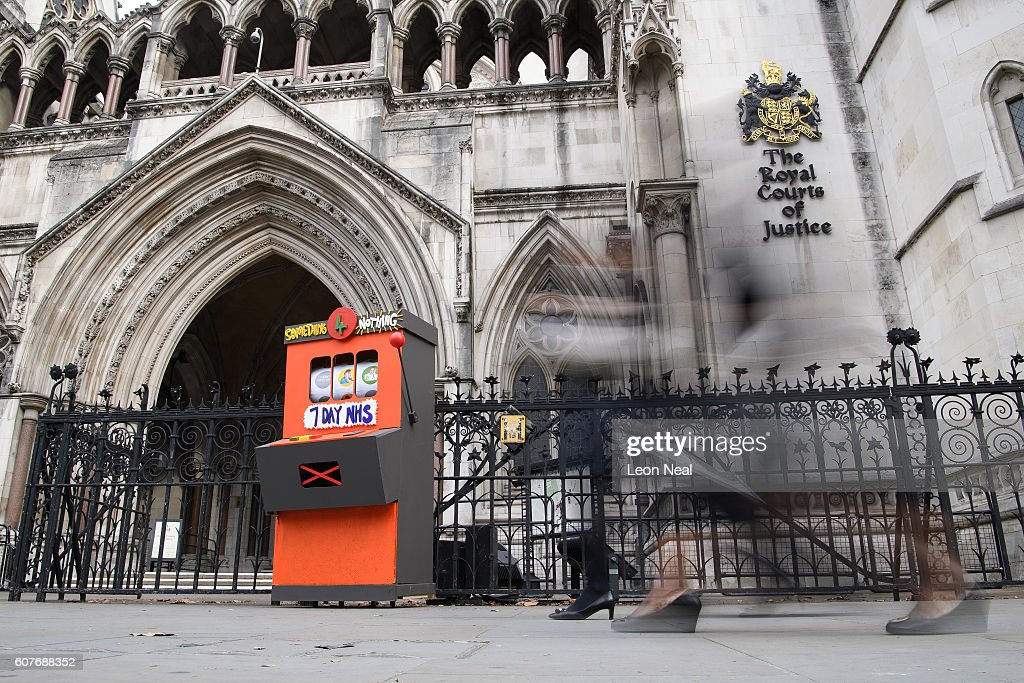 Members of the public walk past a fake slot machine as junior doctors and supporters rally outside the Royal Courts of Justice, Strand on the first day of their hearing as they challenge the government's plan for a seven-day NHS service, on September 19, 2016 in London, England. Justice for Health was founded in March 2015 by five frontline junior doctors to mount a legal challenge against the proposals by Jeremy Hunt, the Secretary of State for Health, to provide a full NHS service over the weekend, despite claims by opponents that the plan is under-funded and has not been fully considered.