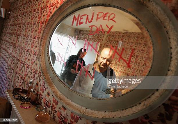 Members of the public walk past a mirror with a Men Per Day tally written in lipstick as part of an art installation entitled 'The Journey Against...