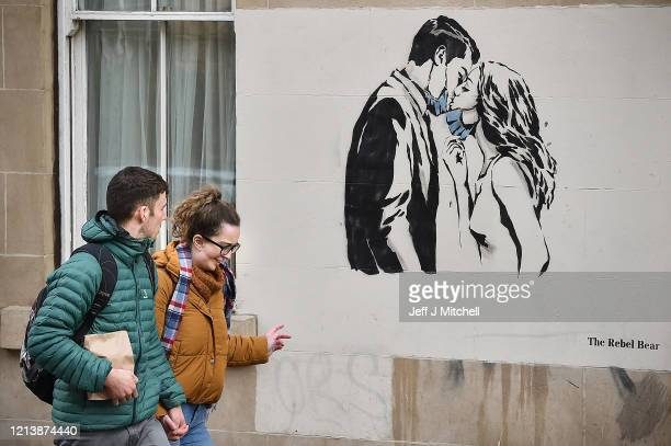 Members of the public walk past a new mural of a mask wearing couple kissing on March 21 2020 in Glasgow Scotland Coronavirus has spread to at least...