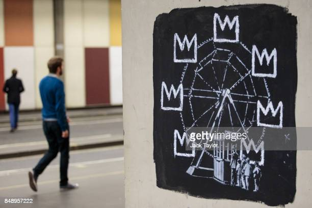 Members of the public walk past a new work by street artist Banksy on a wall by the Barbican Centre on September 18 2017 in London England The two...