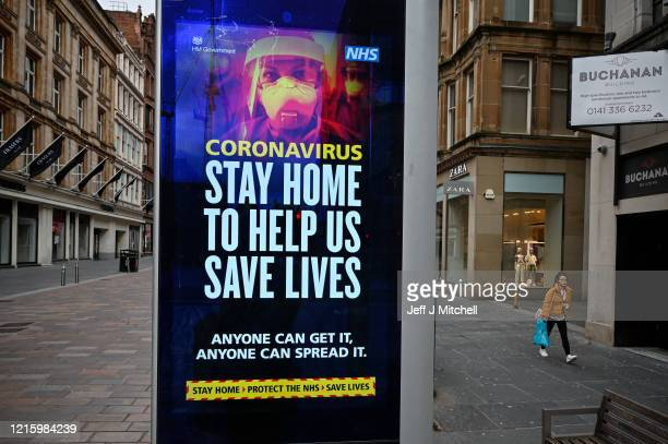 Members of the public walk past a sign asking people to stay at home during the Coronavirus crisis on March 31 2020 in Glasgow Scotland The...