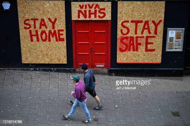 Members of the public walk past a sign on a restaurant in Victoria Street during the Coronavirus crisis on April 16 2020 in Edinburgh The Coronavirus...