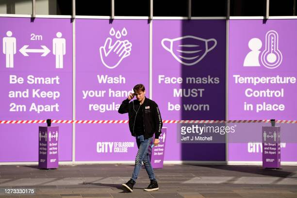 Members of the public walk past coronavirus instruction signs at the City of Glasgow College on September 18, 2020 in Glasgow, Scotland. On September...