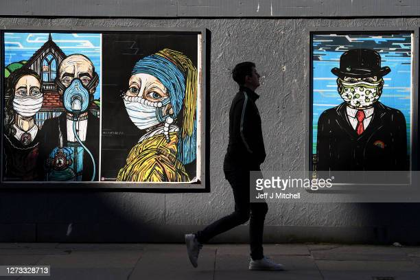 Members of the public walk past coronavirus posters in the Merchant City on September 18 2020 in Glasgow Scotland On September 2 residents of the...