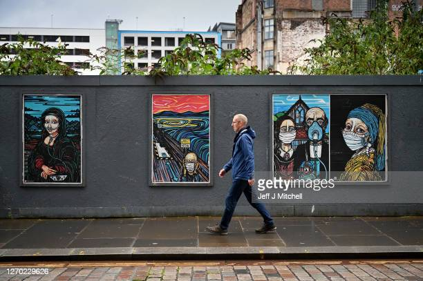 Members of the public walk past coronavirus posters on September 02 2020 in Glasgow Scotland Starting last night Scottish authorities banned people...