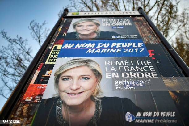 Members of the public walk past election posters of Front National leader Marine Le Pen on February 15 2017 in Henin Beaumont France The former...