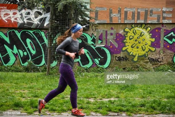 Members of the public walk past graffiti in the Meadows during the coronavirus pandemic on April 17, 2020 in Edinburgh, Scotland.The Coronavirus...