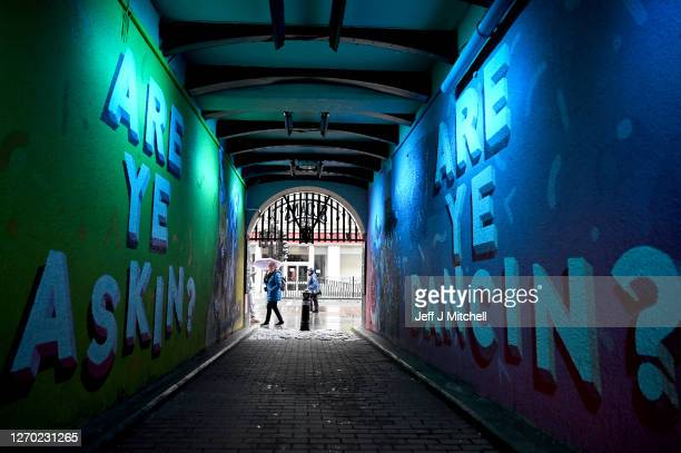 Members of the public walk past graffiti on September 02 2020 in Glasgow Scotland Starting last night Scottish authorities banned people in Glasgow...
