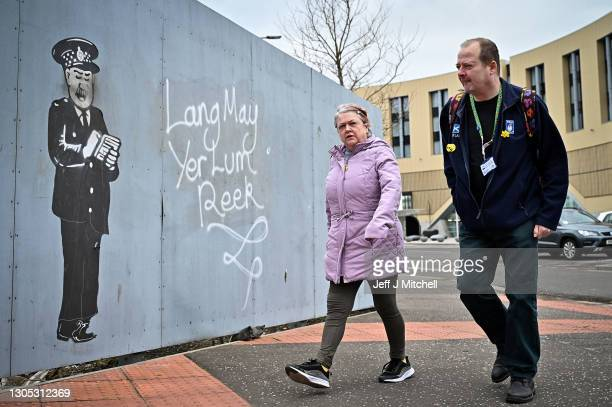 "Members of the public walk past graffiti, saying ""Lang may yer lum reek"" which translates to ""Long may your chimney smoke!"", signifying ""May you live..."