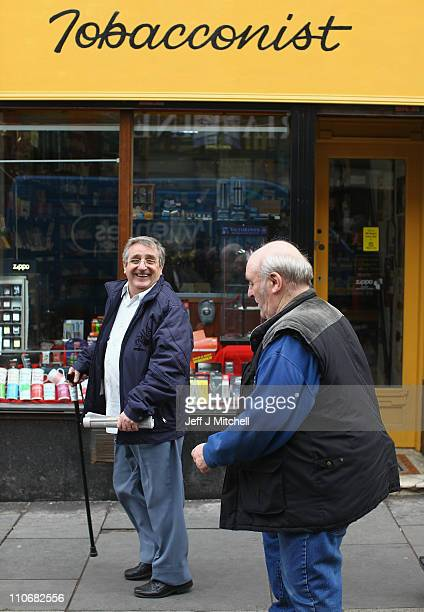 Members of the public walk past James Harvie Tobacconist on March 23 in Paisley Scotland The Chancellor is expected to implement further measures to...