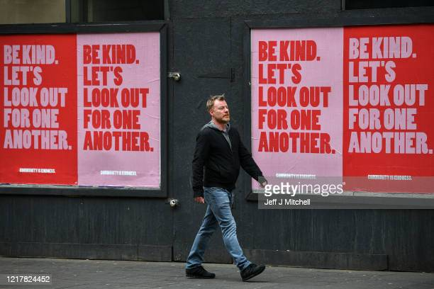 Members of the public walk past new posters placed around the city center on April 9 2020 in Glasgow Scotland There have been around 60000 reported...