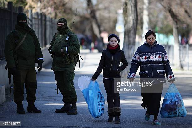 Members of the public walk past Russian military personel outside a Ukrainian Military base on March 17 2014 in Simferopol Ukraine Voters on the...
