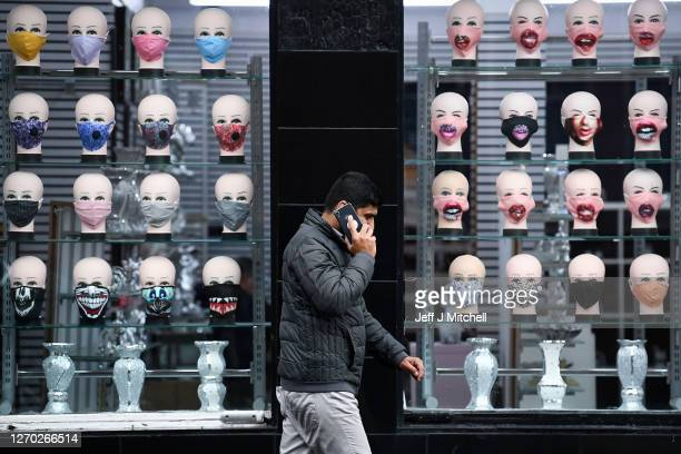 Members of the public walk past s shop selling face coverings on September 02, 2020 in Glasgow, Scotland. Starting last night, Scottish authorities...