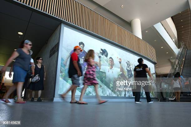 Members of the public walk past sporting images at Optus Stadium on January 21 2018 in Perth Australia The 60000 seat multipurpose Stadium features...