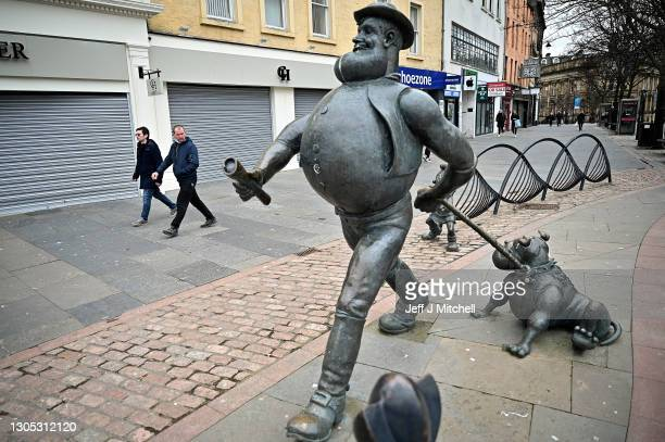 Members of the public walk past the Desperate Dan statue, hero of DC Thomson's 'The Dandy' comics, on March 04, 2021 in Dundee, Scotland. The UK...