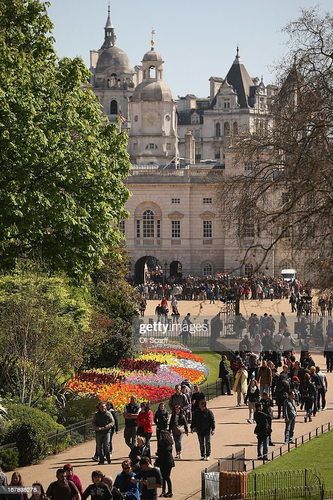 Members of the public walk past tulips in full bloom in St James's Park on May 1, 2013 in London, England. Following an unseasonally cold start to the year, temperatures across the UK are beginning to increase.