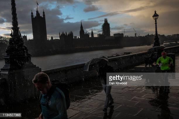 Members of the public walk through a hailstorm at sunset opposite the Houses of Parliament on April 2 2019 in London England The current deadline...