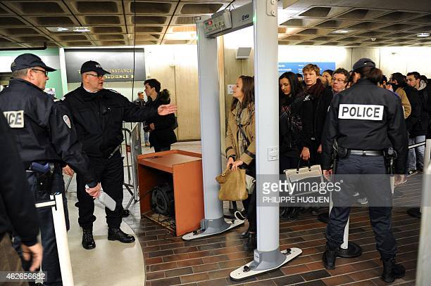Members of the public walk through a metal detector as they arrive at the Lille courthouse northern France on February 2 on the first day of the...