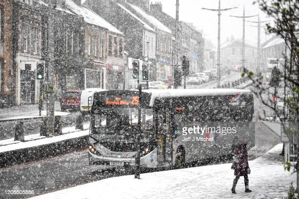 Members of the public walk through a snow shower on February 11 2020 in Lanark Scotland An amber weather warning of heavy snow showers has been...