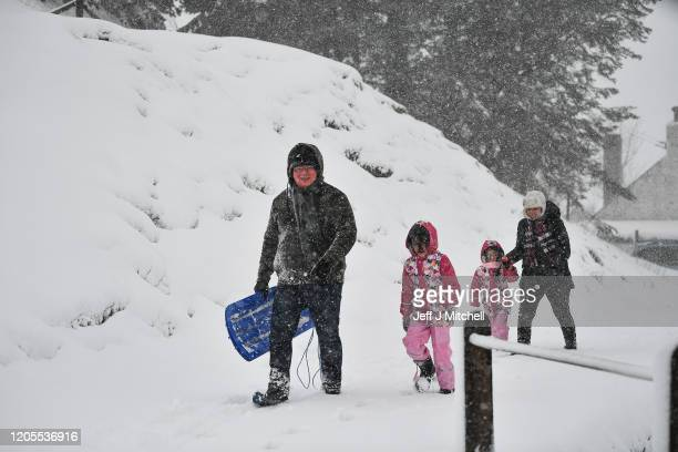 Members of the public walk through a snow shower on February 11 2020 in Wanlockhead Scotland An amber weather warning of heavy snow showers has been...