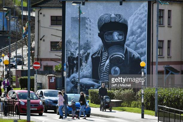 Members of the public walk through the Bogside area as a mural is displayed on a wall in the distance ahead of the Funeral of Martin McGuinness n...