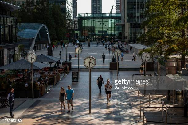 Members of the public walk through the Canary Wharf business district on September 14, 2020 in London, England. Many companies with headquarters in...