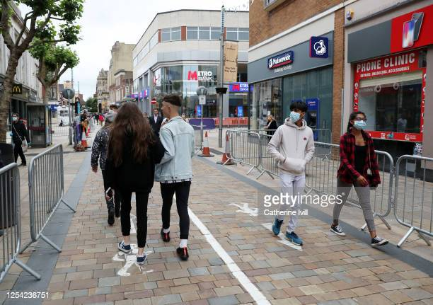 Members of the public walk through the city centre which has been marked out with social distancing markings on July 04, 2020 in Wolverhampton,...