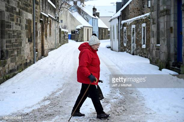 Members of the public walk through the snow on February 9, 2020 in Falkland, Scotland. An amber weather warning is in place until 21:00 for parts of...