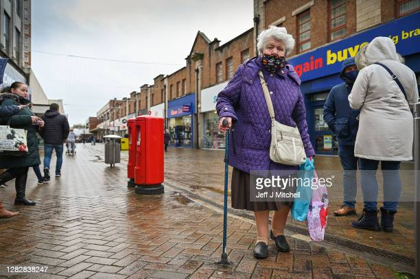 Members of the public walk through the town centre on October 29, 2020 in Motherwell, Scotland. The levels of coronavirus restrictions to be placed...