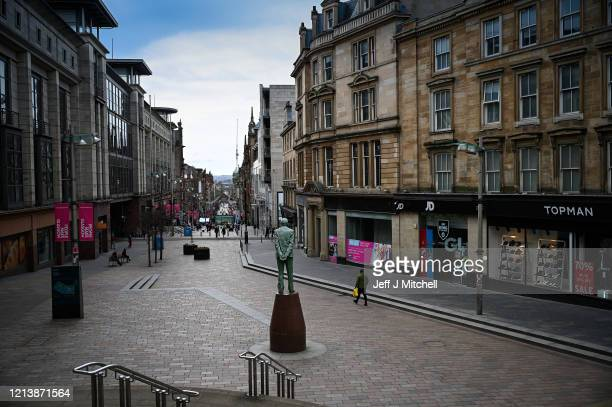 Members of the public walking on Buchanan Street on March 21, 2020 in Glasgow, Scotland. Coronavirus has spread to at least 182 countries, claiming...