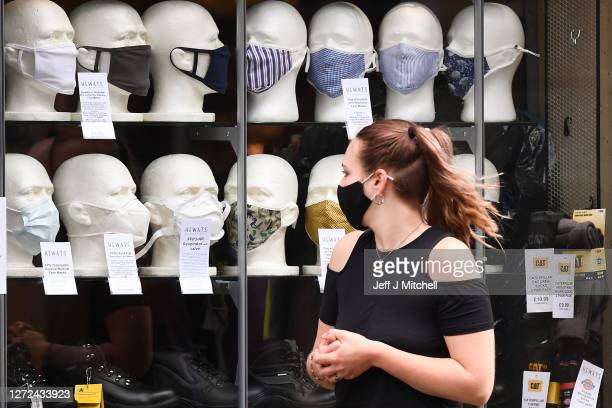 Members of the public walks past a shop window with face masks on display in Princess Street as a new law comes into force limiting social gatherings...