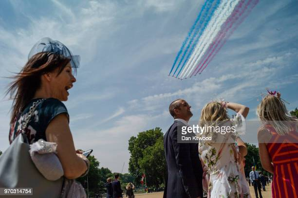 Members of the public watch a flypast by the Red Arrows from Horse Guards Parade after the Trooping The Colour ceremony on June 9 2018 in London...