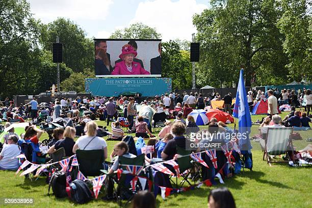 Members of the public watch a large screen in St James's Park showing coverage of the Patron's Lunch a special street party outside Buckingham Palace...