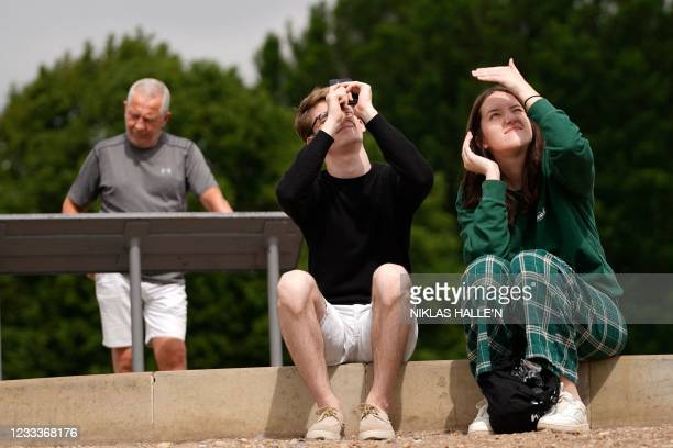 Members of the public watch a partial solar eclipse from Primrose Hill in central London on June 10, 2021.