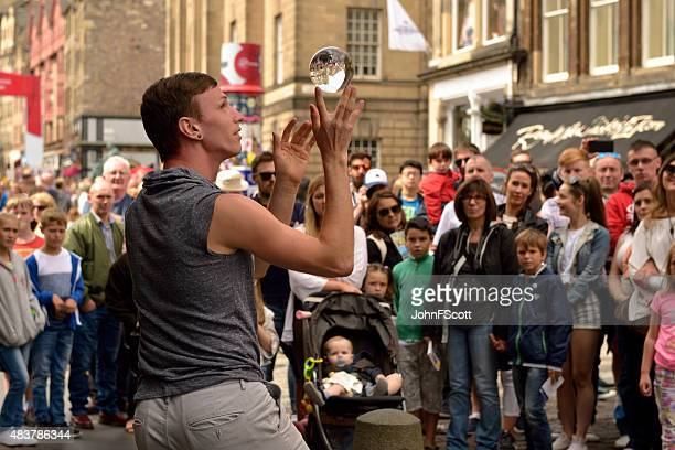 Members of the public watch a street performer in Edinburgh