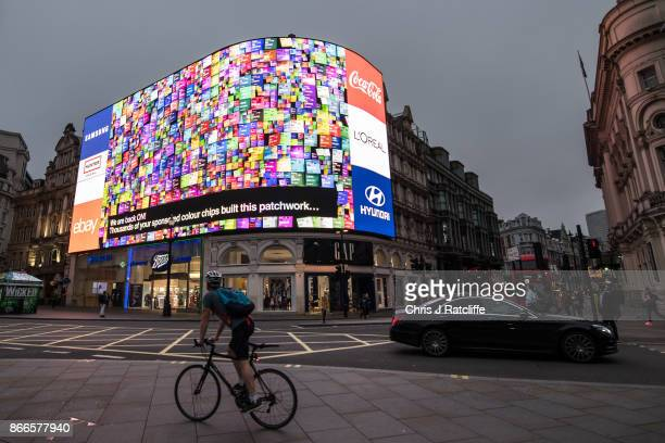 Members of the public watch as an animation is seen after the countdown as the Piccadilly Circus lights are switched back on after a nine month...