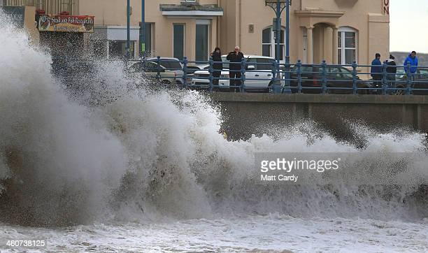 Members of the public watch as high tide waves break along the seafront at Porthcawl on January 5 2014 in Mid Glamorgon Wales After a period of...