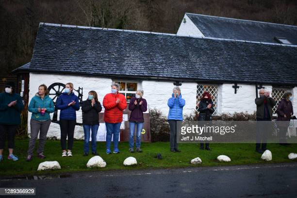 Members of the public watch as the funeral cortege of Dr Hamish MacInnes OBE BEM, mountaineer makes its way through Glencoe on December 4, 2020 in...