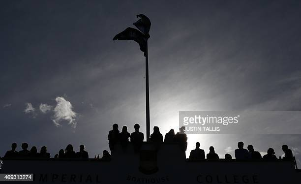 Members of the public watch Oxford women's crew carry their boat out to the River Thames prior to the start of the boat race between Oxford and...
