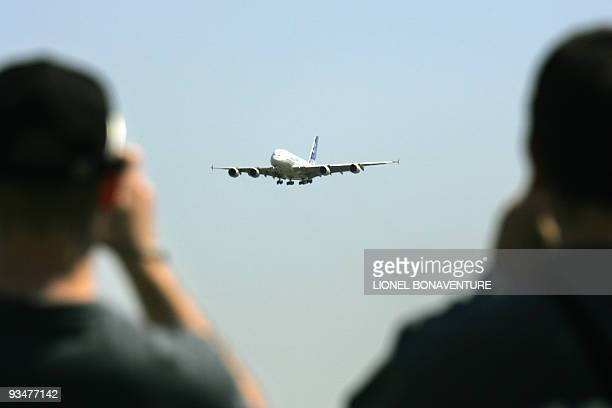 Members of the public watch the landing of the giant doubledecker Airbus A380 the world's largest commercial airliner 27 April 2005 on the tarmac of...