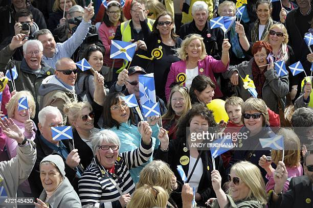 Members of the public wave Saltire flags the national flag of Scotland as they wait for Scottish First Minister and leader of the Scottish National...