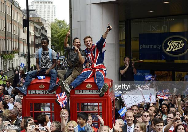 Members of the public wave to the athletes from the top of phone boxes during the London 2012 Victory Parade for Team GB and Paralympic GB athletes...