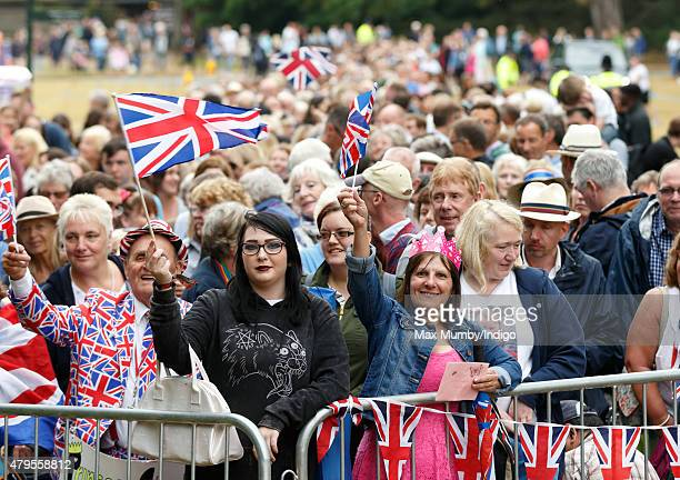 Members of the public wave union flags as they queue outside the church of St Mary Magdalene on the Sandringham Estate prior to the christening of...