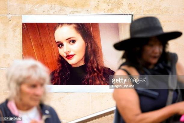 Members of the public wealk past a photo of Grace Millane during a vigil at Civic Square on December 12 2018 in Wellington New Zealand The body of...