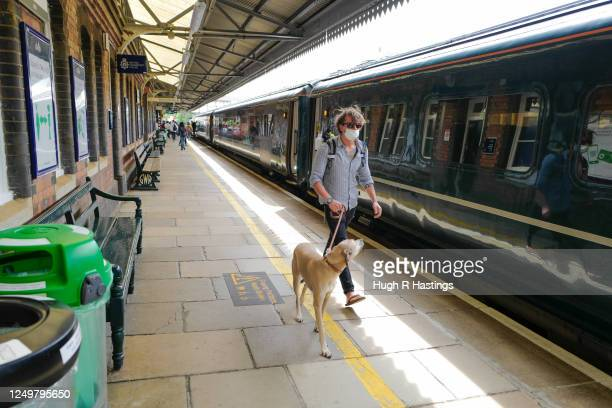 Members of the public wear a face mask at Truro station on June 15, 2020 in Truro, Cornwall. The British government have relaxed coronavirus lockdown...