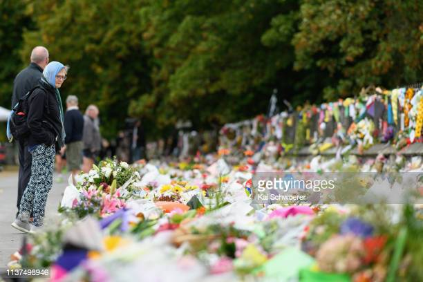 Members of the public wear headscarves as a sign of solidarity as they take a look at flowers and condolences at the entrance to the Christchurch...