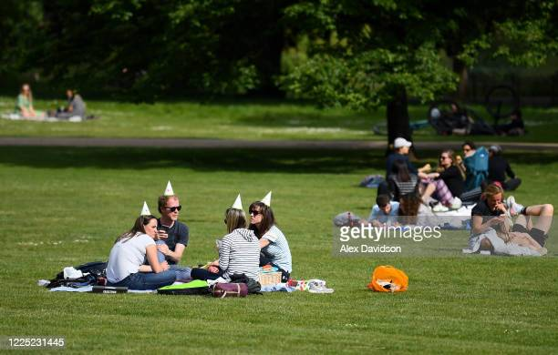 Members of the public wear party hats in St James's Park on May 16 2020 in London England The prime minister announced the general contours of a...