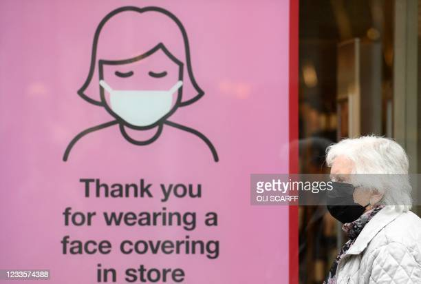 Members of the public wearing a face mask passes a sign asking shoppers to face coverings inside the store, in Cumbria, north west England on June 21...