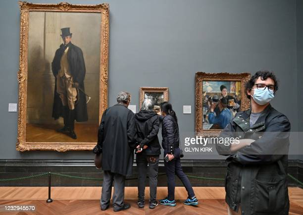 Members of the public wearing face coverings look at artworks displayed inside the re-opened National Gallery in London as Covid-19 lockdown...