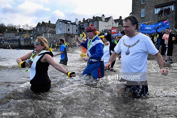 Members of the public wearing fancy dress enter the water as they join around 1000 New Year swimmers many in costume in front of the Forth Rail...